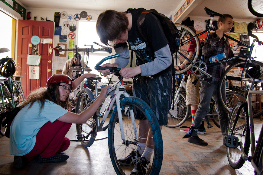 Kids learning how to fix bikes in the classroom.