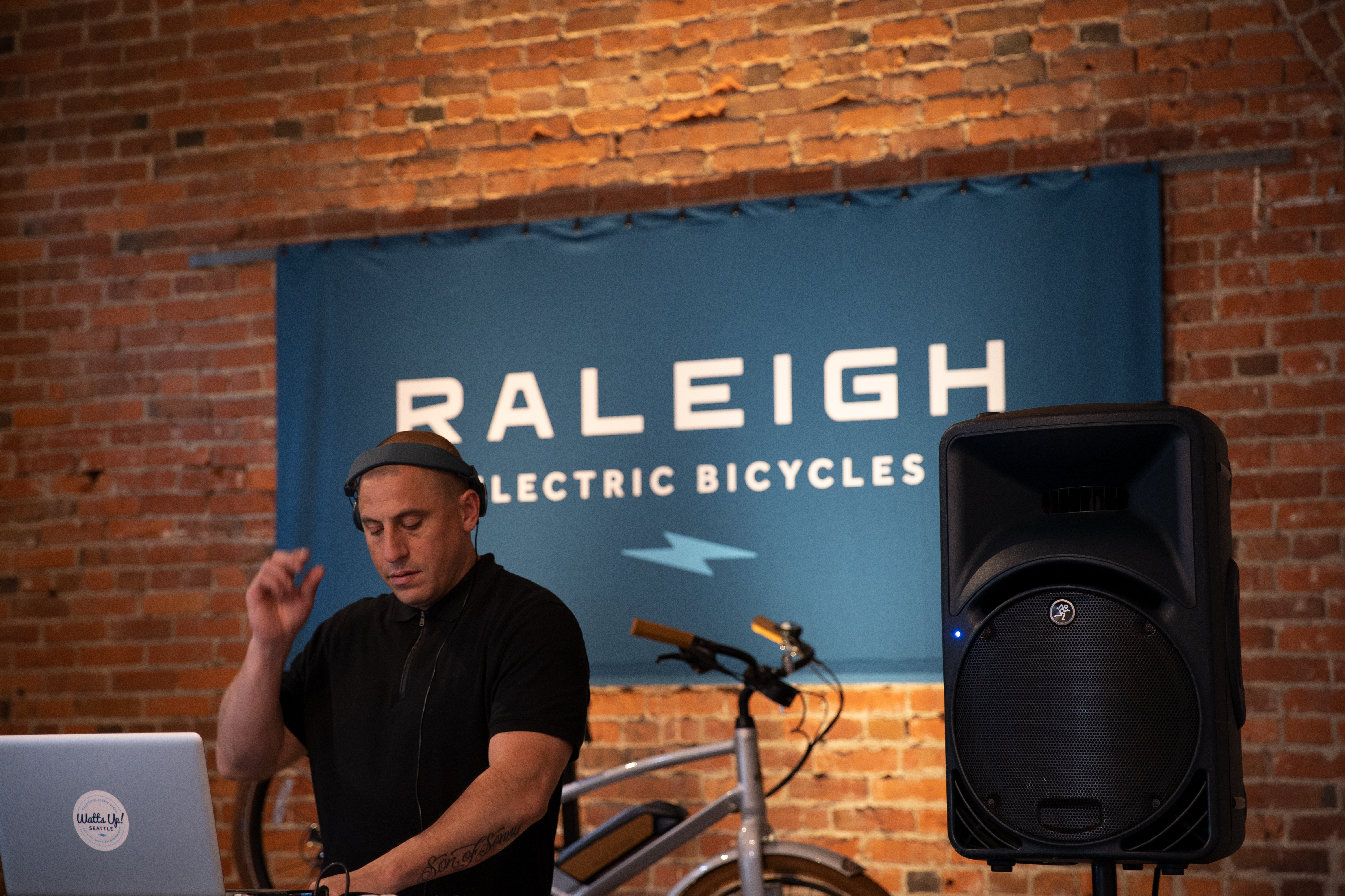 DJ scratching records in front of Raleigh sign