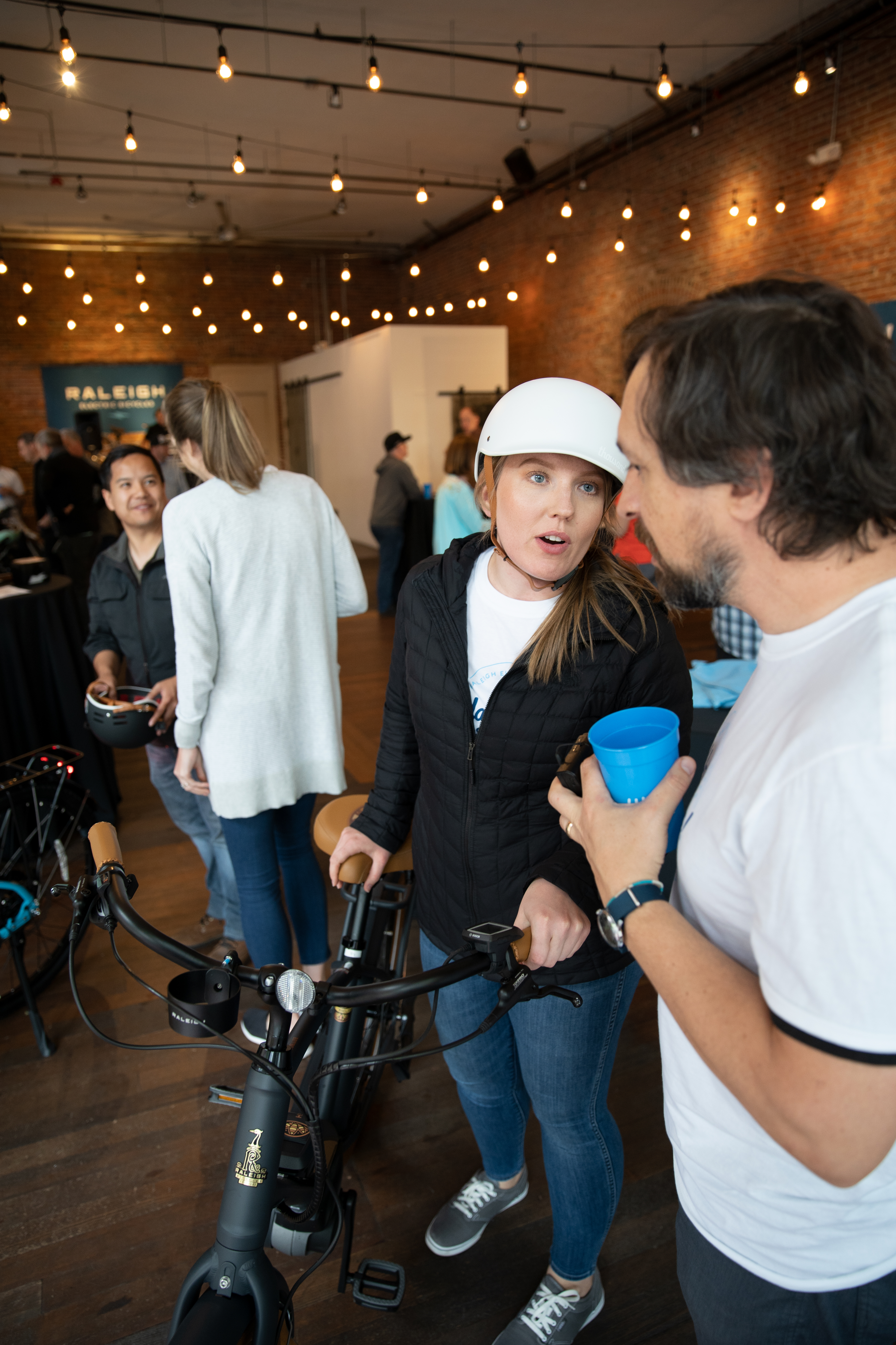 Woman in bike helmet standing next to bike and talking to man standing next to her.