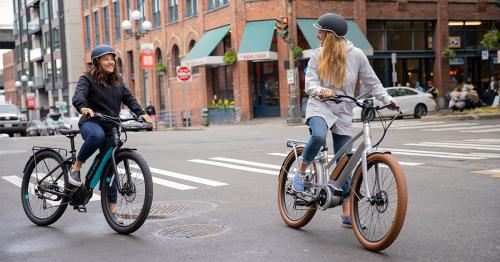 Two women getting ready to start pedaling their electric bikes on a busy city street.